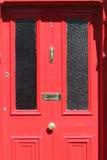 Rote Tür mit Bronzeverzierungen Stockfotografie