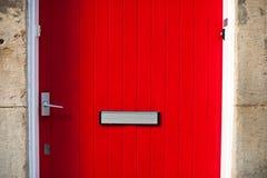 Rote Tür mit einem Briefschlitz Stockfotos