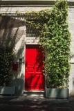 Rote Tür und weiße Jasminumanlage stockfotografie