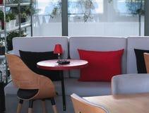 Rote Tabelle auf dem Hintergrund eines weißen Sofas lizenzfreie stockbilder