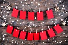 Rote Tags mit dem Kopien-Raum, der im Schnee auf hölzernem Hintergrund hängt Lizenzfreies Stockbild