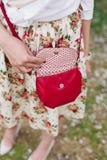 Rote Tasche der Nahaufnahme in den Händen der Frau auf der Straße Lizenzfreies Stockbild