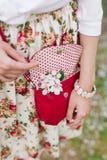 Rote Tasche der Nahaufnahme in den Händen der Frau auf der Straße Lizenzfreie Stockfotos
