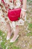 Rote Tasche der Nahaufnahme in den Händen der Frau auf der Straße Stockbild