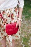 Rote Tasche der Nahaufnahme in den Händen der Frau auf der Straße Stockfotos