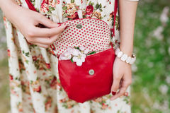 Rote Tasche der Nahaufnahme in den Händen der Frau auf der Straße Lizenzfreie Stockfotografie