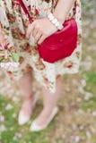Rote Tasche der Nahaufnahme in den Händen der Frau auf der Straße Lizenzfreie Stockbilder