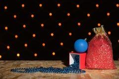 Rote Tasche des neuen Jahres mit einem Geschenk und Perlen auf einem Holztisch auf einem Ba Stockfotografie