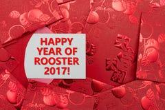 Rote Taschen mit einem Karte geschriebenen glücklichen Jahr des Hahns Lizenzfreies Stockbild