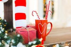 Rote Tasse Tee oder Kaffee oder heißes chokolate mit Bonbons und Geschenk - Weihnachtsfeiertags-Hintergrund lizenzfreie stockbilder