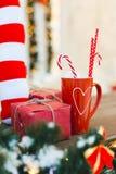 Rote Tasse Tee oder Kaffee oder heißes chokolate mit Bonbons und Geschenk - Weihnachtsfeiertags-Hintergrund lizenzfreies stockfoto