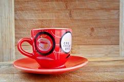 Rote Tasse und Untertasse auf einem hölzernen Hintergrund Stockbild