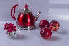 Rote Teekanne, Nektarinen und Blumenstrauß von Gartennelken Stockbilder
