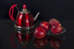 Rote Teekanne, Nektarinen und Pfirsich Stockbild