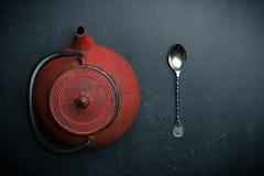 Rote Teekanne und silberner Löffel auf dunklem Hintergrund stockfoto