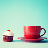Rote Teeschale der Weinlese und kleiner Kuchen Stockfotos