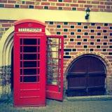 Rote Telefonzelle auf einem Hintergrund eine Backsteinmauer Stockfoto