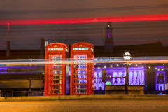 Rote TELEFONZELLEN nachts in London, England Stockbilder