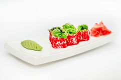 Rote tobiko Sushirolle geflochten auf einer weißen Platte Stockfotografie