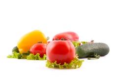 Rote Tomate mit Gemüse auf weißem Hintergrund Stockfoto