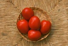 Rote Tomaten auf der Weidentabelle Stockfoto
