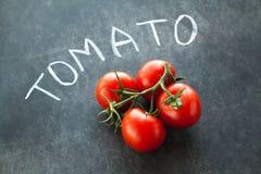 Rote Tomaten auf grüner Niederlassung Stockbilder