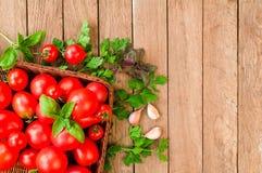 Rote Tomaten in einem Weidenkorb auf einem Holztisch lizenzfreies stockfoto