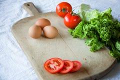 Rote Tomaten, Kopfsalat, Eier, auf dem alten hölzernen Hintergrund Prozess für die Zubereitung eines vegetarischen Frühstücks Stockfoto