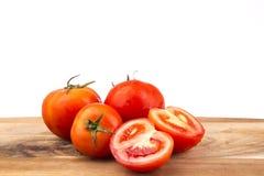 Rote Tomaten mit Brett auf einem weißen Hintergrund Stockbilder