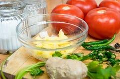 Rote Tomaten mit Gewürzen und Kräutern auf einem hölzernen Brett in der Küche stockfoto