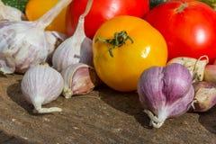Rote Tomaten und gelbe Tomaten, Knoblauch Stockbilder