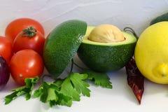 Rote Tomaten und grüne Avocado mit Zitrone auf weißem Hintergrund, Guacamole lizenzfreies stockbild