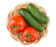 Rote Tomaten und grüne Gurken im Weidenkorb auf Weiß Stockbild