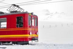 Rote Tram parkt am Hügel an schneiendem Tag Lizenzfreie Stockbilder