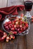 Rote Trauben auf einem Weinlesebehälter mit Glas Wein Stockbild