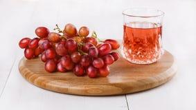 Rote Trauben auf hackendem Brett mit Glas des spritzy Getränks Lizenzfreies Stockbild