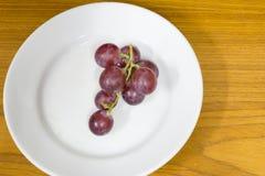 Rote Trauben auf Platte Stockfotografie