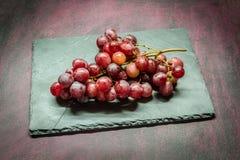 Rote Trauben auf Stein Stockfoto