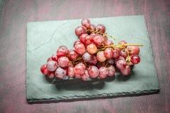 Rote Trauben auf Stein Stockfotografie
