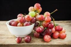 Rote Trauben der frischen Frucht auf hölzernem Hintergrund Lizenzfreies Stockbild