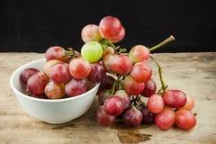Rote Trauben der frischen Frucht auf hölzernem Hintergrund Stockfoto