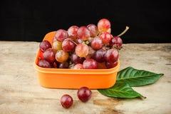 Rote Trauben der frischen Frucht auf hölzernem Hintergrund Stockbilder