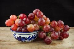Rote Trauben der frischen Frucht auf hölzernem Hintergrund Stockbild
