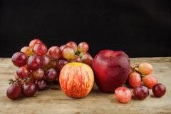 Rote Trauben der frischen Frucht und roter Apfel auf hölzernem Hintergrund Stockfotografie