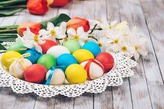 Rote Tulpe und farbige Eier Farbige Ostereier und Frühlingsblumen auf weißem hölzernem Hintergrund Lizenzfreies Stockbild