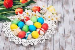 Rote Tulpe und farbige Eier Farbige Ostereier und Frühlingsblumen auf weißem hölzernem Hintergrund Stockbilder