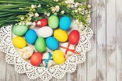 Rote Tulpe und farbige Eier Farbige Ostereier und Frühlingsblumen auf weißem hölzernem Hintergrund Lizenzfreie Stockfotos
