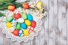 Rote Tulpe und farbige Eier Farbige Ostereier und Frühlingsblumen auf weißem hölzernem Hintergrund Stockfoto