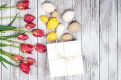 Rote Tulpe und farbige Eier Farbige Ostereier und rote Tulpen auf hölzernem Hintergrund Beschneidungspfad eingeschlossen Stockfoto