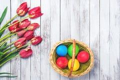 Rote Tulpe und farbige Eier Farbige Ostereier und rote Tulpen auf hölzernem Hintergrund Beschneidungspfad eingeschlossen Raum für Stockbilder
